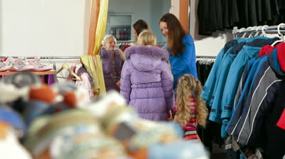 stock-footage-mother-with-two-daughters-shopping-for-girls-clothes-in-a-clothing-store-child-trying-on-warmest